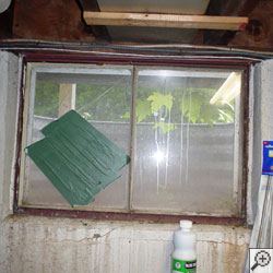 An old, rusted basement window with a steel frame in Kearney.