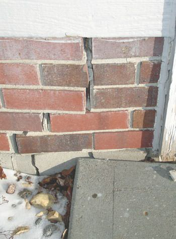 Severe street creep damage to a garage wall outside a Denison home